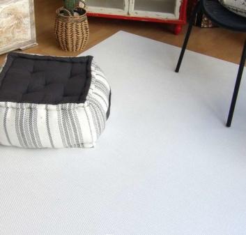 Alfombra blanca y cojín de suelo